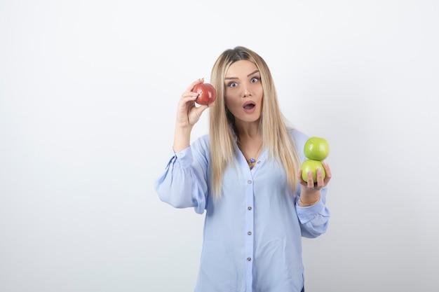 Portretfoto van een vrij aantrekkelijk vrouwenmodel dat en verse appelen bevindt zich houdt.