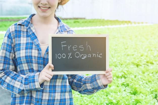 Portretfoto van jonge aantrekkelijke mooie aziatische vrouw die verse groentesalade van haar bord van de de handgreep van het hydrocultuurlandbouwbedrijf met ruimte voor verwoording oogsten.