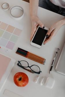 Portretfoto van kantoorbenodigdheden op wit en vrouwelijke handen met zwarte manicure, met smartphone.