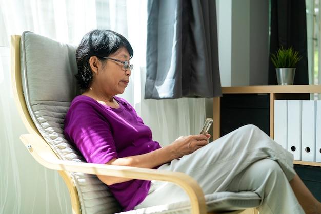 Portretfoto van oudere of oude aziatische pensioneringsvrouw die en smartphone glimlacht gebruikt voor het controleren van sociale media terwijl het aanbrengen op fauteuil in de woonkamer. technologie, communicatie en mensenconcept