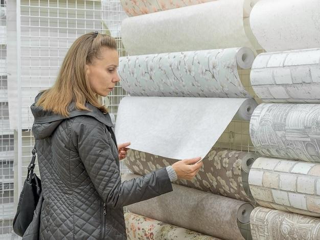 Portretfoto van vrouw kiest behang in de bouwwinkel. vrouw selecteert behang op de planken in de winkel.