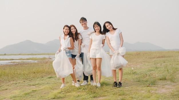 Portretgroep jonge multi-etnische vrijwilligers helpt de natuur schoon te houden, kijkend naar voren en glimlachen met witte vuilniszakken op het strand