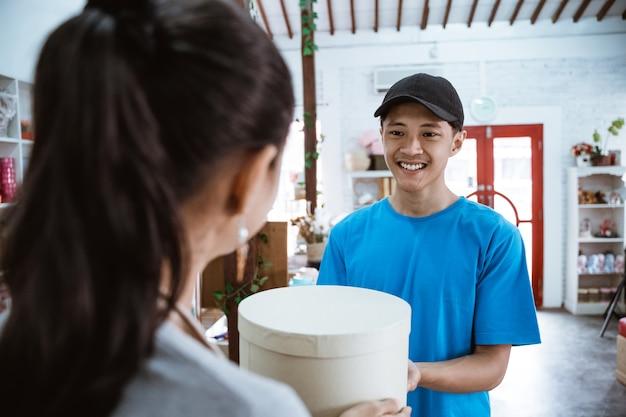 Portretkoerier die glimlachend het pakket brengt voor jonge vrouwelijke winkelier die een pakket van koerier ontvangt