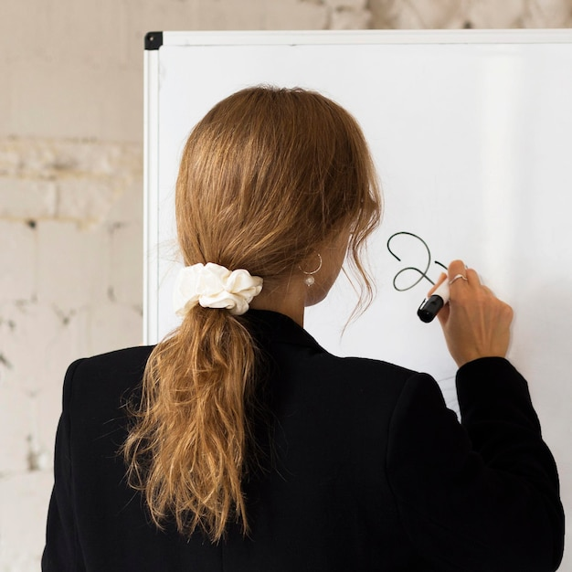 Portretleraar die op wit bord schrijft