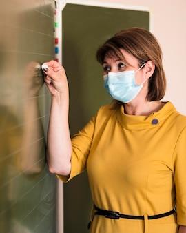 Portretleraar met masker schrijven op schoolbord