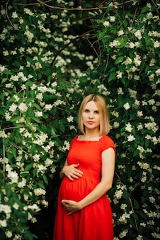 Portretmedium van zwangere vrouw met bloemen wordt geschoten die