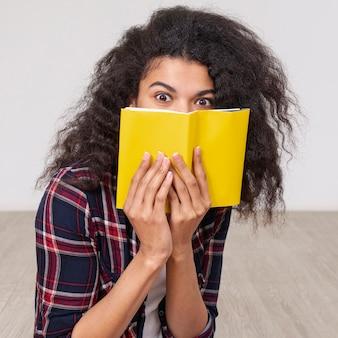 Portretmeisje die haar gezicht behandelen met boek