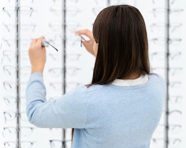 Portretmeisje die in oogglazenopslag paar kiezen