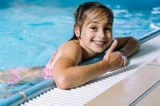 Portretmeisje die pret in binnenzwembad hebben. het meisje rust in het waterpark.