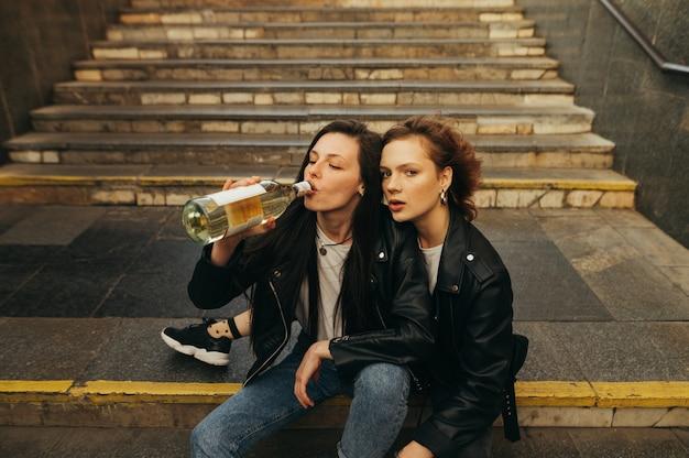 Portretmeisjes in leren jassen en jeans die wijn drinken uit een fles op de trap