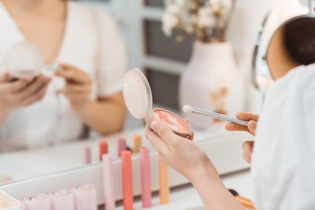 Portretmening van jonge volwassen aziatische vrouw die spiegel bekijkt, die in lichte ruimte zit en make-up maakt. mooie en professionele visagist die penseel en blusher gebruikt