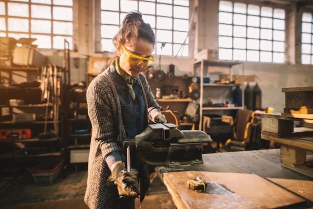 Portretmening van tevreden glimlachende midden oude professionele vrouwelijke timmerwerkarbeider met staalbankschroef op de lijst in de workshop.