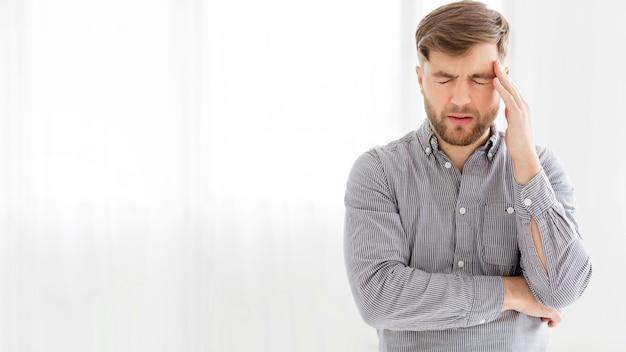 Portretmens met hoofdpijn met exemplaar-ruimte