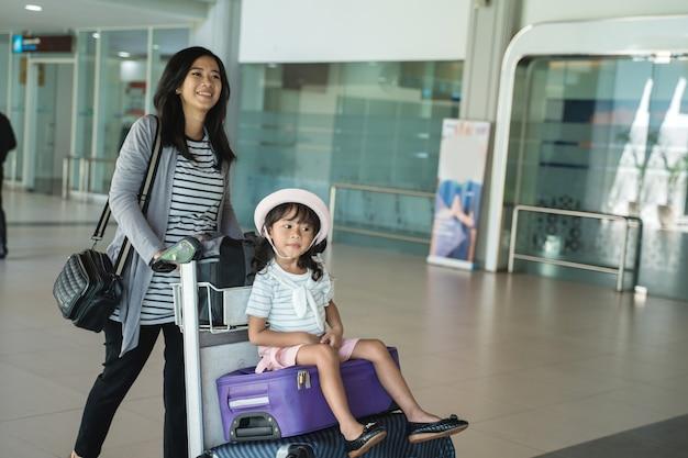 Portretmoeder en zijn dochter die met karretje lopen