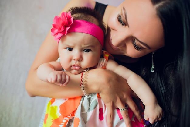 Portretmoeder met haar oude baby van 3 maanden in slaapkamer