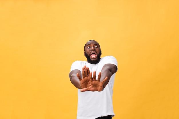 Portretschok en geïrriteerde ontevreden jongeman die zijn handen opstak om daar geen stop te zeggen