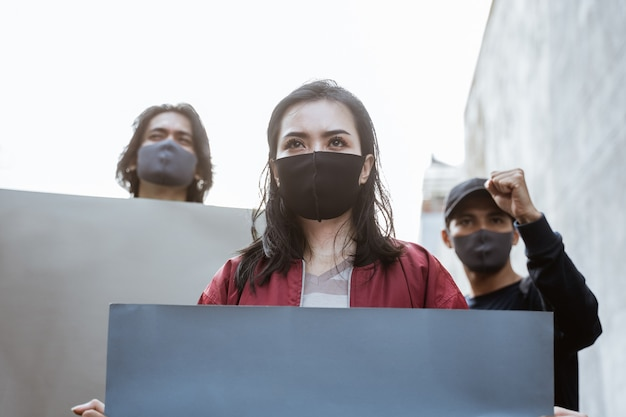 Portretstudenten die blanco papier vasthouden en demonstraties houden door gezondheidsprotocollen te volgen
