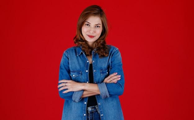 Portretstudio-opname van een 45-jarige aziatische vrouw die jeandkleren draagt en poseert voor de camera met een glimlach en zelfvertrouwen op een rode achtergrond.