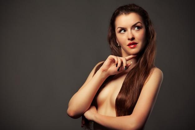 Portretten van een mooi kaukasisch jong slank bruinharige topless meisje op een grijze