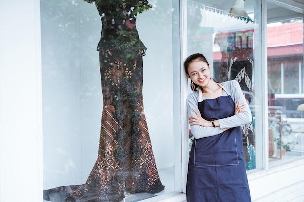 Portretten van jonge vrouwelijke verkopers met gekruiste arm die naast een zijraam staan en traditionele batikkleding met etalagepop verkopen, zijn voorbeelden