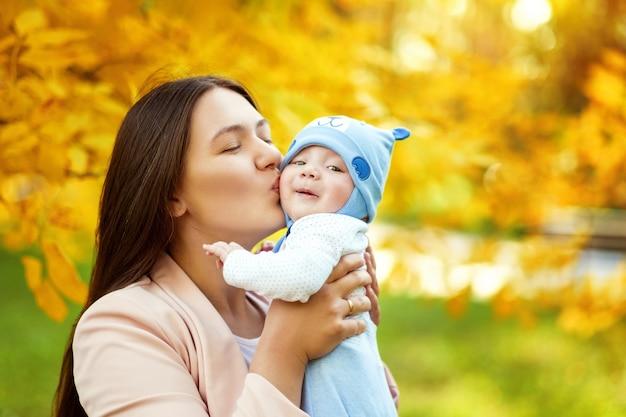 Portretten van moeder en baby in herfst park, moeder knuffels en kussen baby Premium Foto