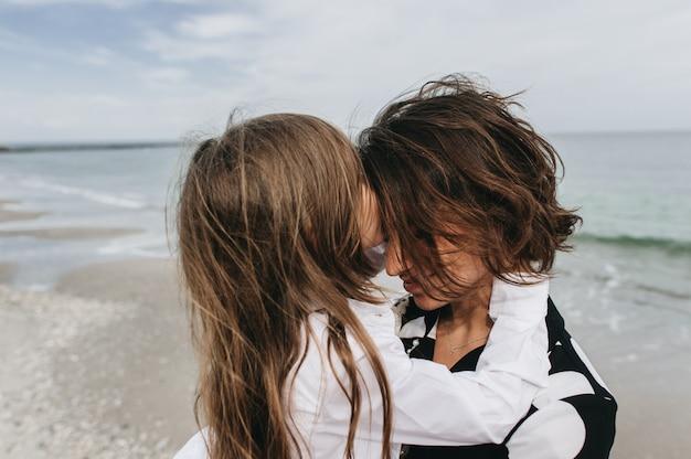 Portretten van moeder en dochter op het zee strand