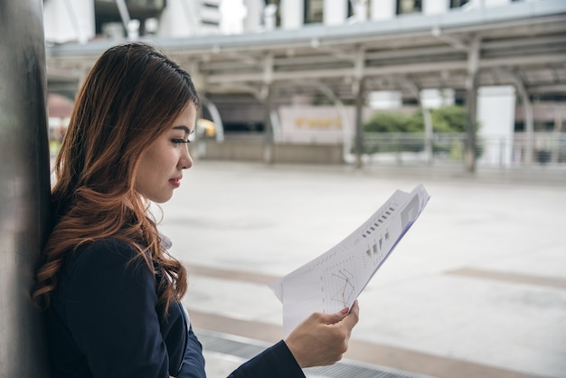 Portretten van mooie aziatische vrouw in denkende uitdrukking die met financiële grafiek werkt