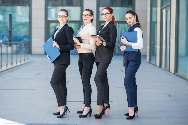 Portretten van mooie succesvolle jonge bedrijfsvrouwen met tabletten en omslagen in handen