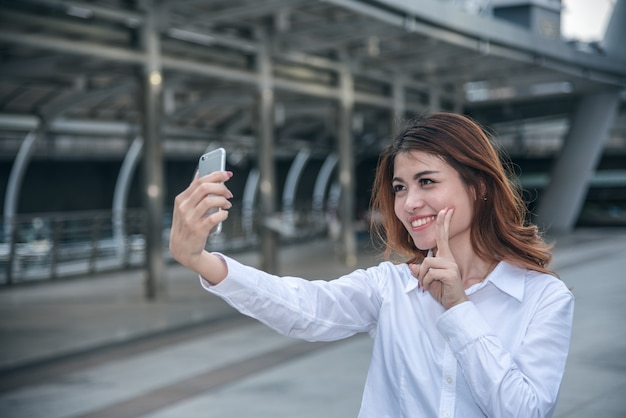 Portretten van vrij mooie aziatische vrouw die een foto nemen door selfie in stedelijk.