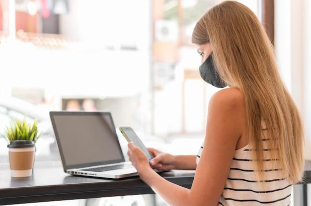Portretvrouw bij terras met laptop die masker dragen