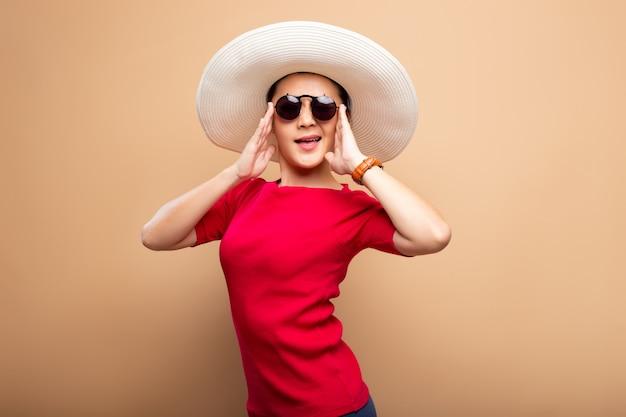 Portretvrouw die grote die hoed dragen op bruine beige achtergrond wordt geïsoleerd
