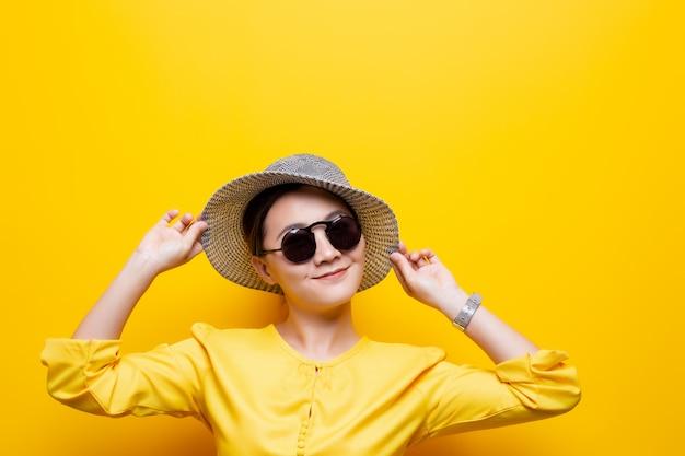 Portretvrouw die zonnebril en hoed dragen die over gele achtergrond wordt geïsoleerd