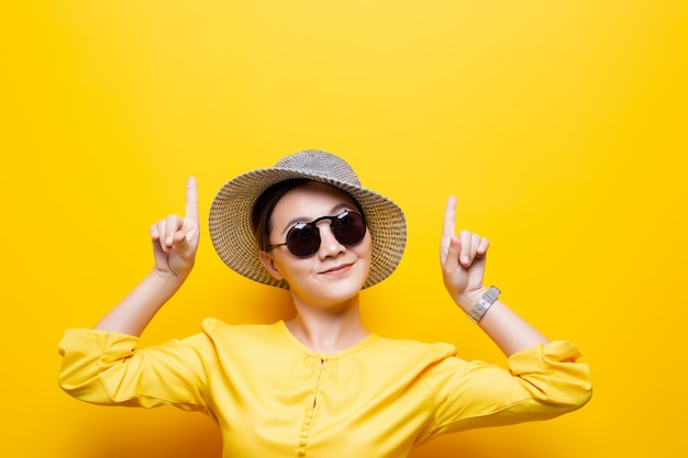 Portretvrouw die zonnebril en hoedenpunt dragen die omhoog aan exemplaarruimte over gele achtergrond wordt geïsoleerd