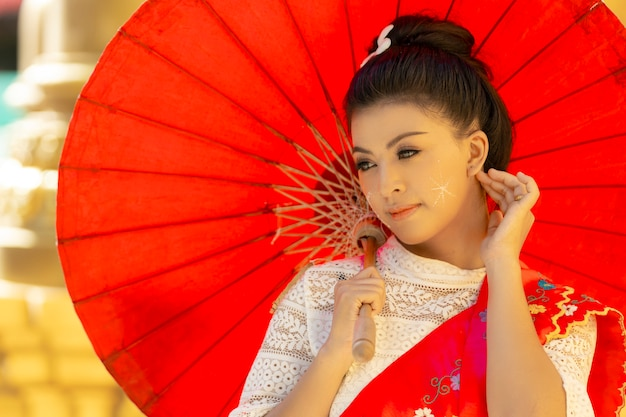 Portretvrouw in birmese klederdracht, draagt een rode paraplu.