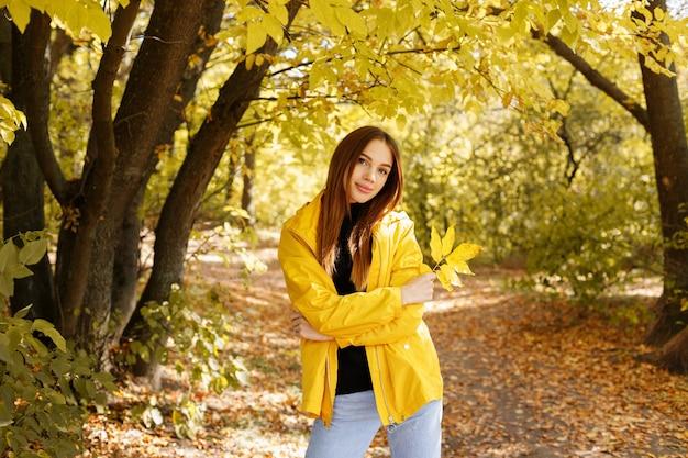 Portretvrouw in een herfstgele regenjas voor het herfstgele bos op een wandeling. herfststemming