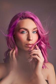 Portretvrouw met felgekleurd vliegend haar, alle tinten paars. haarkleuring, mooie lippen en make-up. haar wapperen in de wind