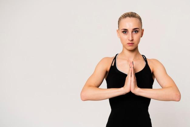 Portretvrouw met handen bij borst worden verenigd die