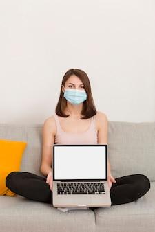 Portretvrouw op laag met laptop
