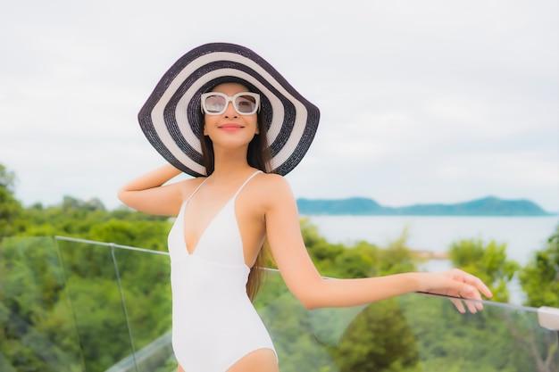 Portriat mooie jonge aziatische vrouw gelukkig glimlach rond balkon met uitzicht op zee