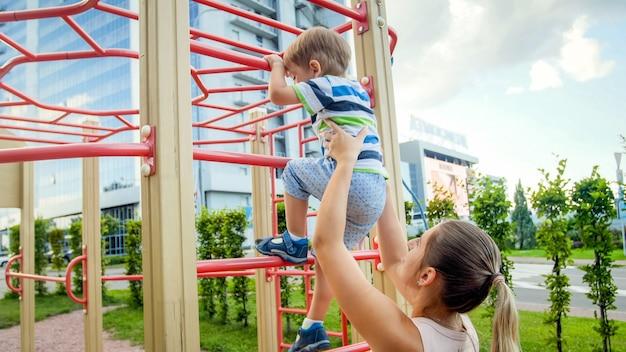 Portriat van een jonge moeder die haar 3-jarige kindzoon ondersteunt en vasthoudt op een metalen ladder op een kinderspeelplaats in het park