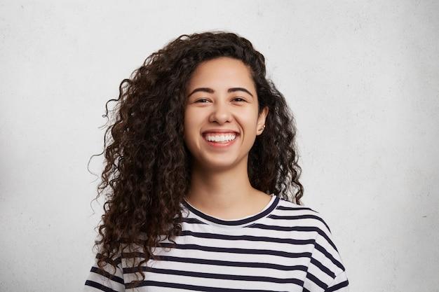 Portriat van mooie krullende vrouw draagt een gestreept zwart-wit t-shirt, glimlacht gelukkig als blij