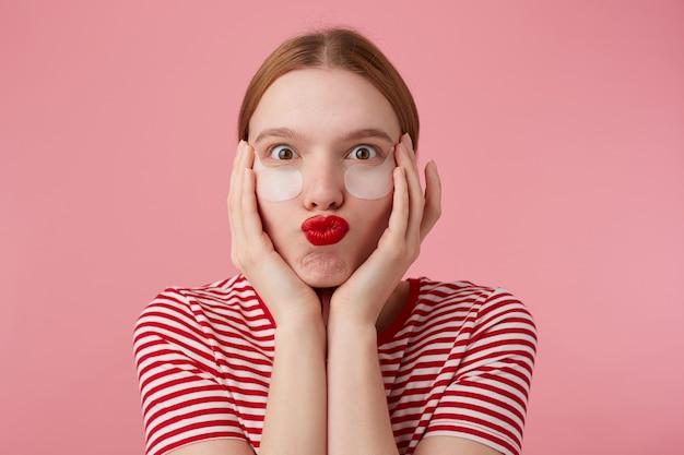 Portrit van grappige mooie jonge gelukkige roodharige dame in een rood gestreept t-shirt, met rode lippen, raakt zijn gezicht met de handpalmen, erg blij met nieuwe plekken. staat.