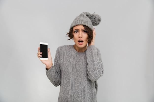 Porttrait van geschokte jonge vrouw in trui en hoed