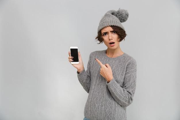 Porttrait van verwarde jonge vrouw in trui en hoed