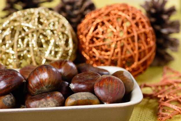 Portugese noten in keramische container over gele jute en met kerstversieringen