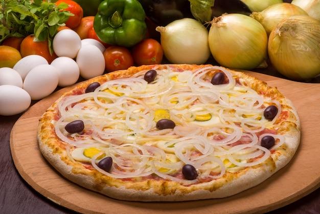 Portugese pizza met gekookte eieren, ui en olijven op een houten bord en groenten op de achtergrond.
