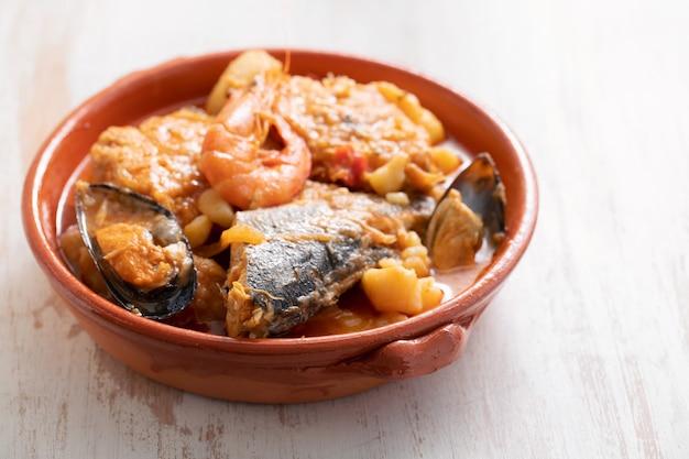 Portugese vis en zeevruchtenstoofpot in schotel op ceramisch oppervlak