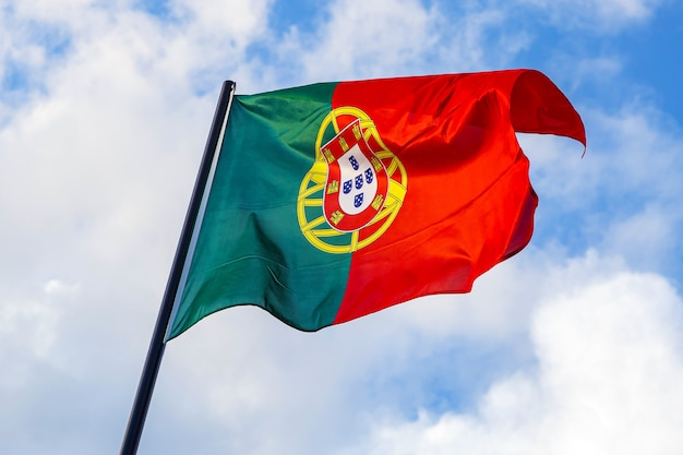 Portugese vlag die voor een blauwe hemel golft.