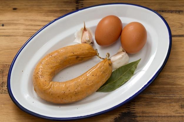 Portugese worstalheira met eieren op witte schotel