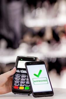 Pos-terminal, betaalmachine met mobiele telefoon op de winkel. contactloos betalen met nfc-technologie